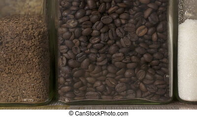 Containers with roasted coffee beans, instant coffee and...