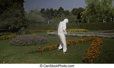 Contaminated biologist worker in hazmat suit decontaminated...