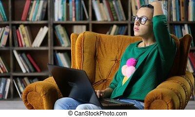 Contemplating female freelancer working on laptop - Pensive...
