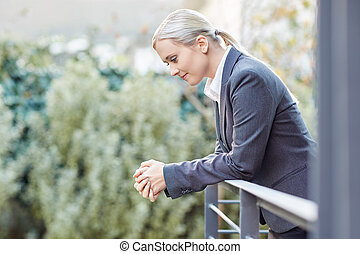 Contemplating her career - A young businesswoman leaning ...