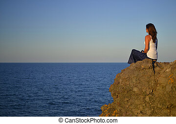 Contemplating - Beautiful young woman sitting on a rock...