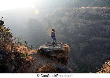 A young Indian guy contemplating on a rock near a valley.