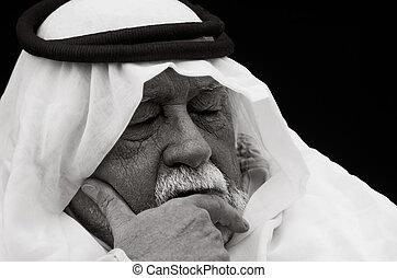 Contemplation - An older gentleman wearing Arabic headdress...
