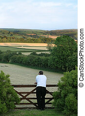 Rear view of a man standing in front of a wooden gate and over looking freshly cut hay fields in rural countryside in early evening.
