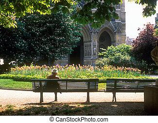 Spring in Paris. Senior woman sitting on the bench.