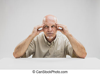 Contemplative balding man sitting at table