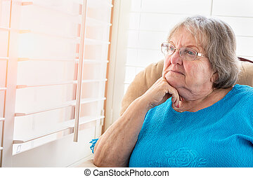 Contemplative Senior Woman Gazing Out of Her Window