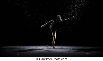 Contemporary ballet, a man performs elements of modern choreography and jumps in the spotlight. Silhouette of a dancer against the background of falling snow. Slow motion