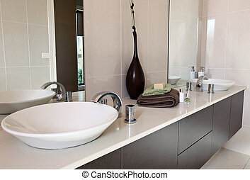 Modern bathroom, with double round sinks. Earthy tones of beige and brown.
