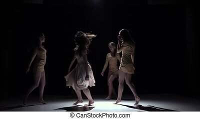 Contemporary dance continue of three girls in white dresses, on black, shadow, slow motion