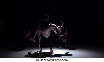 Contemporary dance of five dancers on black, shadow, slow motion