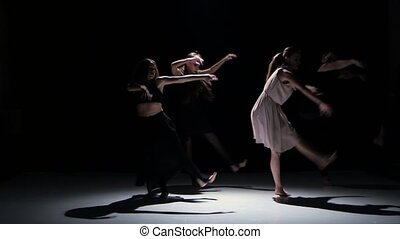 Contemporary dance performance of five dancers on black, shadow