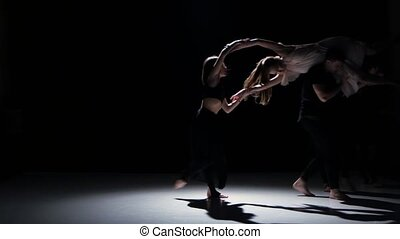 Contemporary dance performance of four dancers on black, shadow
