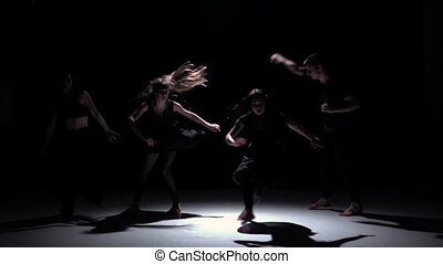 Contemporary dance performance of four talanted dancers on black, shadow, slow motion