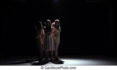Contemporary dance start of three girls in white dresses, on black, shadow, slow motion