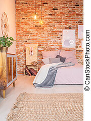 Contemporary decor of cozy room with bed and red brick wall