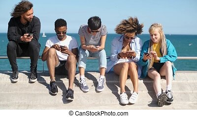 Contemporary diverse friends with smartphones on seafront -...