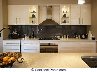 Modern kitchen, with granite benchtops and reflective glass splashback.