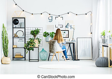 Contemporary office room - Young girl with long hair sits on...