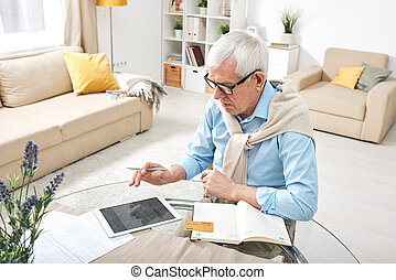 Contemporary old man with digital tablet and bank card booking tickets online