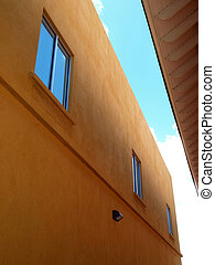 Contemporary two story stucco building and windows