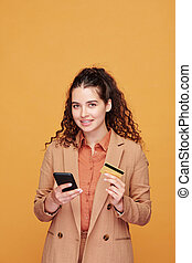 Contemporary young female with smartphone and plastic card going to make order
