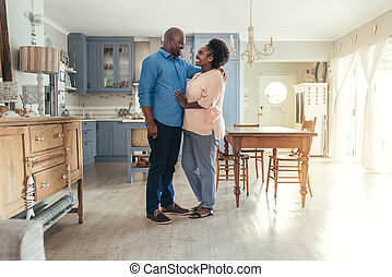 Content African couple standing together in their kitchen