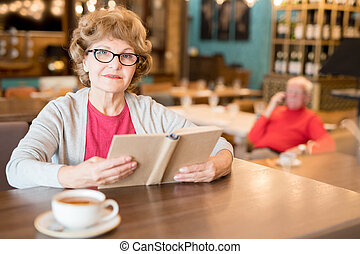 Content attractive senior lady with book