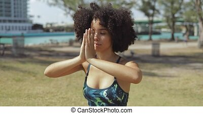 Content black woman meditating with eyes closed