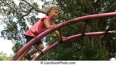 Content boy climbing on playground - Side view of little...
