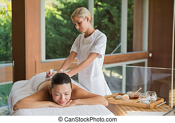 Content brunette enjoying a herbal compress massage at the...