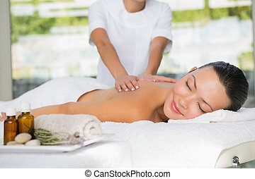 Content brunette getting a back massage