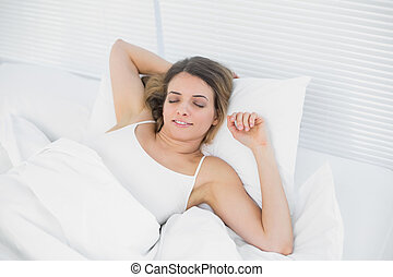 Content brunette woman relaxing lying on her bed