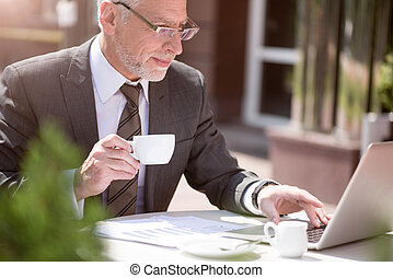 Content businessman drinking coffee
