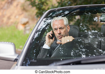 Content businessman on the phone driving expensive cabriolet...