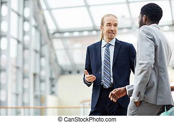 Content businessmen chatting in corridor