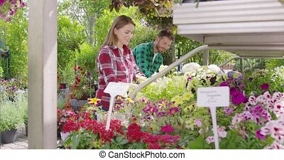 Content couple planting flowers together - Cheerful young...