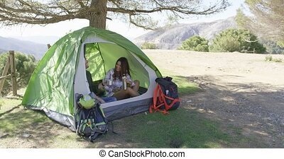 Content couple sitting in tent under trees - Young happy...