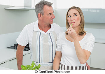 Content couple standing together in kitchen