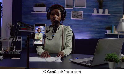 Content creator looking at smartphone camera while talking at mic checking sound during podcast. Online show On-air production internet broadcast host streaming live video, recording digital social