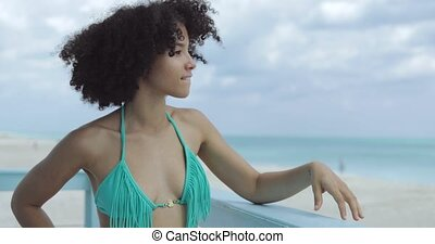 Content dreaming girl on beach tower - Young charming black...