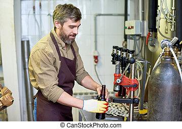 Content handsome technician putting beer in bottles at...