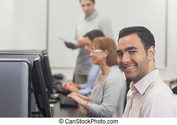 Content mature student sitting in computer class