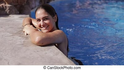 Content model relaxing in pool - Young charming woman...