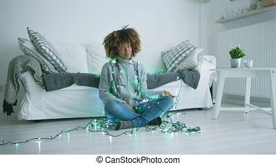 Content model with glowing garland - Wonderful curly woman...