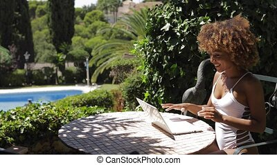 Content model with laptop in resort - Young ethnic woman in...