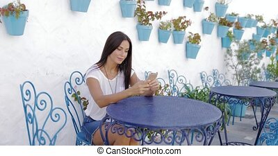 Content model with phone in garden - Pretty young woman in...