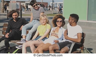Content multiethnic friends on street bench - Group of cool...