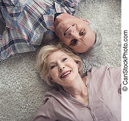Content pensioners relaxing on carpet