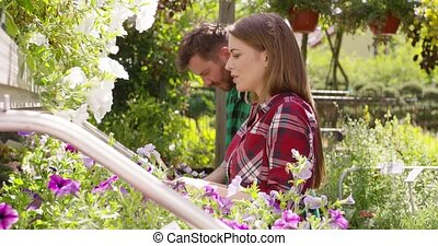 Content people maintaining flowers in garden - Side view of...